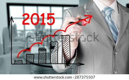 business man drawing growth graph for year 2015 - stock photo