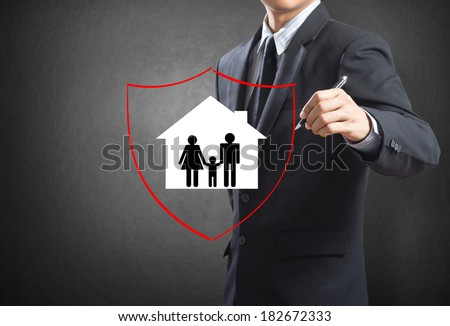 Business man drawing shield protecting family and house, insurance concept - stock photo