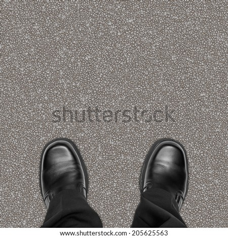 Business man feet on road asphalt, overhead view - stock photo