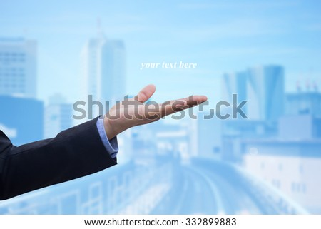 business man gesture open hand over blurred city space background:human hand express blank space for your message on blur urban modern city wallpaper concept:business concept. - stock photo
