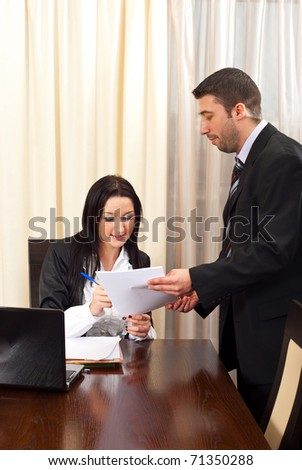 Business man giving a contract for signing to a business woman sitting on chair at table - stock photo