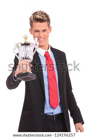 Business man giving you a trophy cup with pride - stock photo