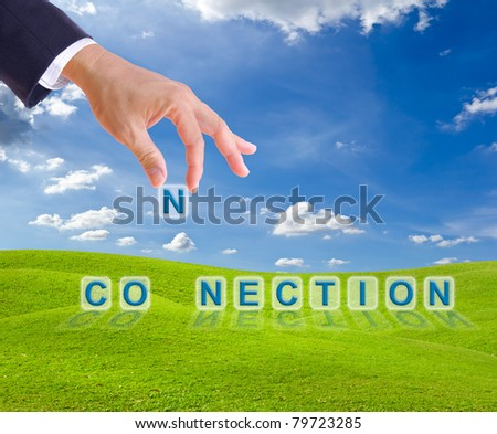 business man hand and connection word buttons on green grass meadow - stock photo