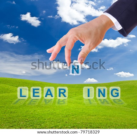 business man hand and learning word on green grass meadow - stock photo