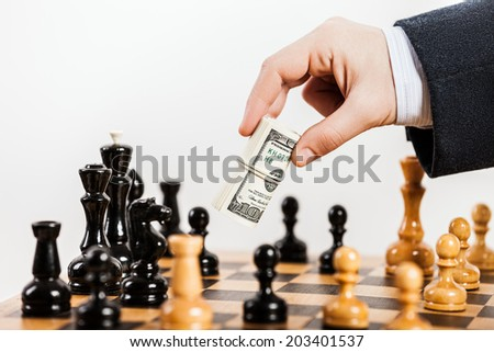 Business man hand holding dollar currency unfair playing chess game - stock photo