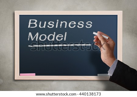 Business man hand holding white chalk with word Business Model on chalkboard. Business concept in small business aspiration.  - stock photo