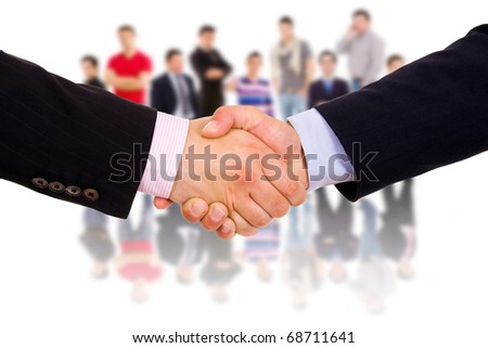 Business man hand shake with colleagues in the background. - stock photo
