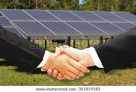 business man hand shake with solar cell blur background - stock photo