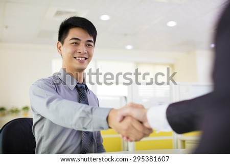 business man hand shaking in office - stock photo