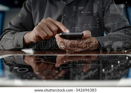 business man hand working on digital tablet computer and smart phone with digital layer business strategy and social media diagram on wooden desk - stock photo