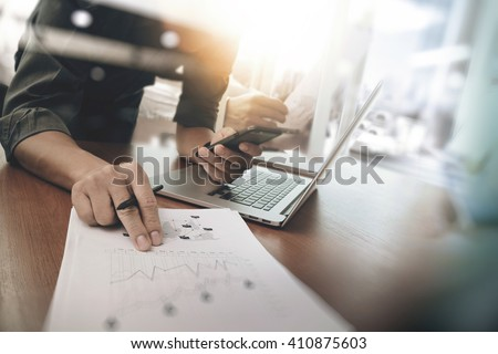 business man hand working on laptop computer with digital layer business graph information diagram on wooden desk as concept - stock photo