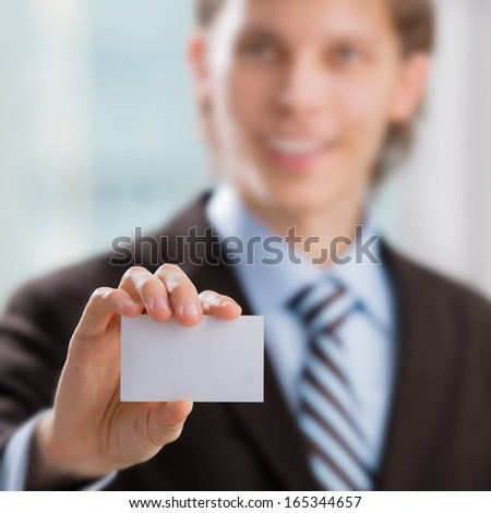 Business man handing a blank business card at his office - stock photo