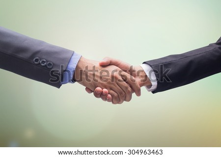 business man handshake over blurred backgrounds, business hands concept - stock photo