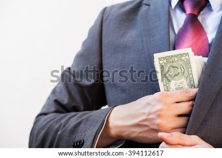 Business man hiding money in jacket pocket - Corruption and Fraud Concept - stock photo