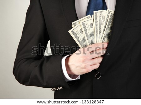 Business man hiding money in pocket on grey background - stock photo