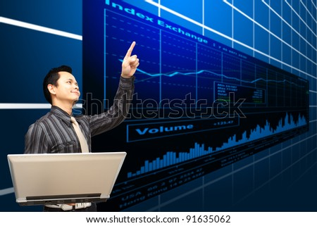 Business man hold notebook computer and stock exchange graph - stock photo
