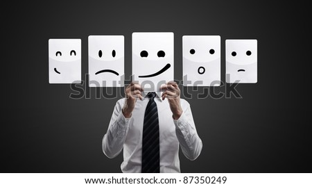 Business man holding a card with smiling face. Man chooses an emotional faces. On a black background - stock photo