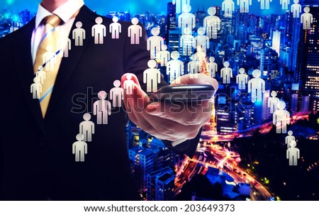 Business man holding a cellphone with human icons - stock photo