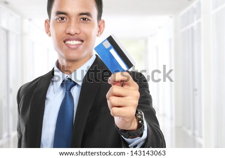 business man holding a credit card and smile on white background - stock photo