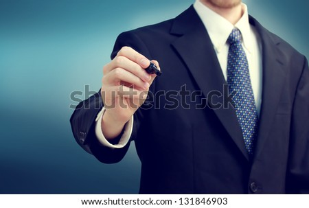 Business man holding a pen on blue background - stock photo