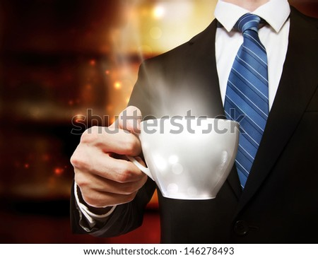Business man holding a steaming cup of hot coffee - stock photo