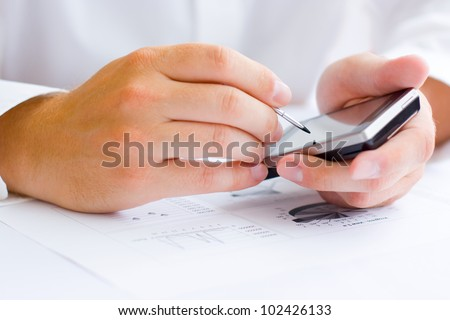Business man holding a touchscreen mobile - stock photo