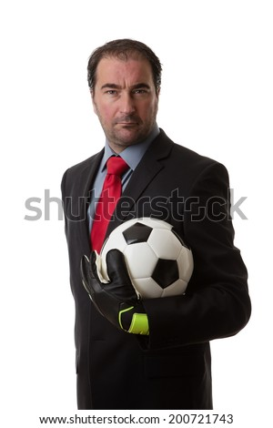 Business man holding a traditional black and white football wearing goalie gloves - stock photo