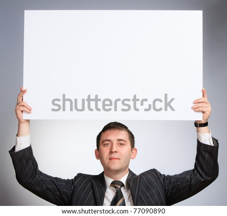 business man holding a white card looking very serious - stock photo