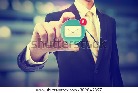Business man holding an email icon on blurred cityscape background  - stock photo