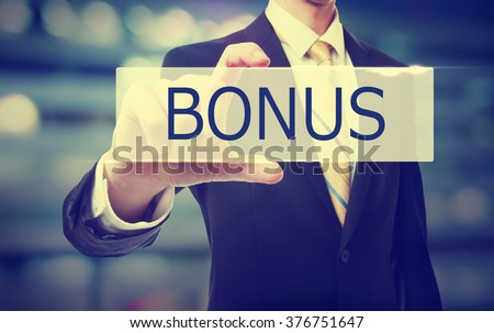 Business man holding Bonus on blurred abstract background   - stock photo