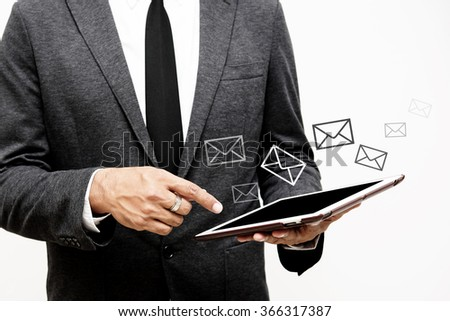 business man holding computer tablet and letter graphics selective focus on pointing finger - stock photo