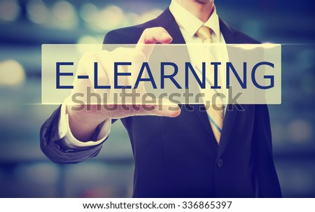 Business man holding E-learning on blurred abstract background   - stock photo