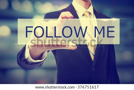 Business man holding Follow Me on blurred abstract background   - stock photo