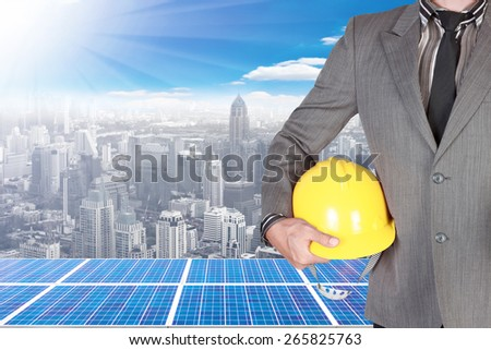 business man holding helmet and solar energy panels on high building against beautiful sky with in concept ecology and real estate - stock photo