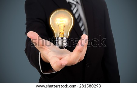 Business man holding light bulb - stock photo