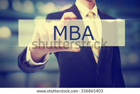 Business man holding MBA on blurred abstract background   - stock photo