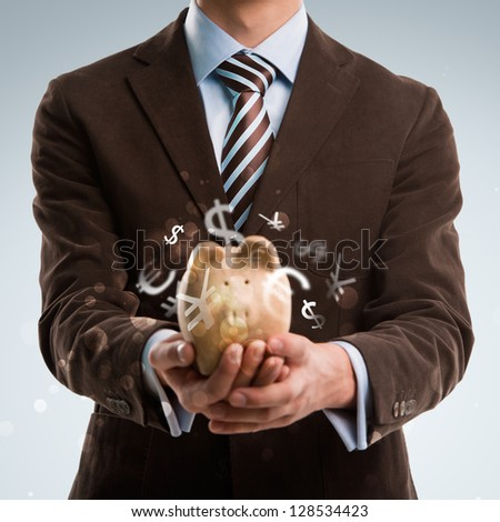Business man holding piggy bank, currency symbols flying around it - stock photo