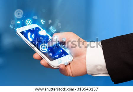 Business man holding smart phone with media icons concept on background - stock photo