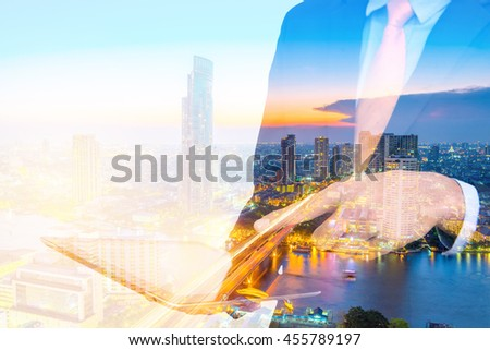 business man holding tablet and using touchpad with Double exposure city background. - stock photo