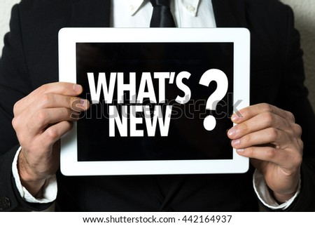 Business man holding tablet with the text: Whats New? - stock photo