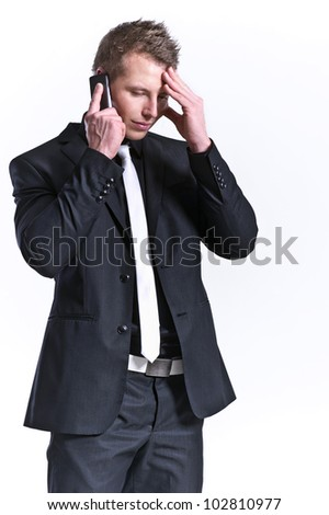 business man in a black suit and a mobile phone with headache is - stock photo