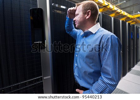 Business man in a data center looking frustrated with the current system. He is looking for a better IT solution. - stock photo