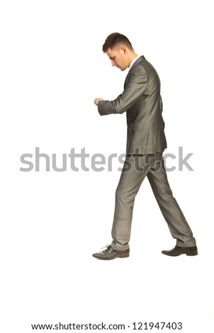 Business man in a hurry walking at work and checking time isolated on white background - stock photo