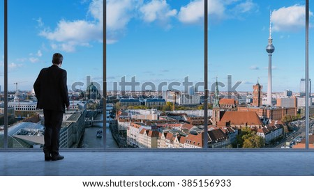 Business man in a loft looking at skyline of Berlin in Germany (3D Rendering) - stock photo
