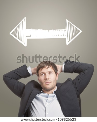 Business man in chair thinking with arrows in different directions over his head - stock photo