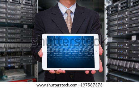 Business man in data center room with touch pad - stock photo