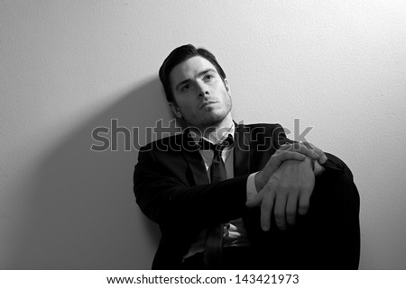 Business man in deep thought resting against the wall - stock photo
