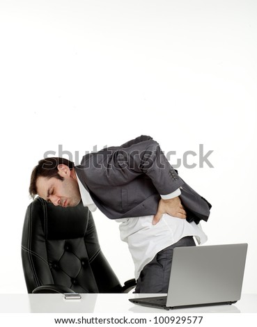 Business man in his office in pain holding his back - stock photo