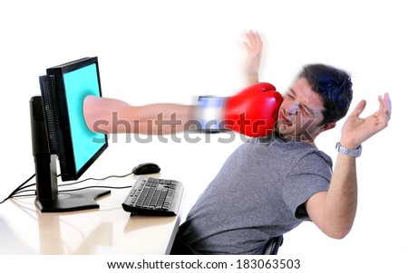 Business man in office with computer hit by boxing glove comming out of monitor  in overwork, frustration, stress and crisis concept isolated on white background  - stock photo