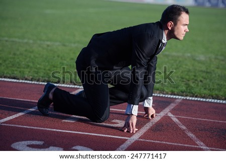 business man in start position ready to run and sprint on athletics racing track - stock photo